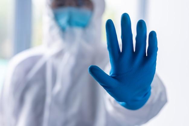 Ppeスーツ、マスク、顔面シールドを身に着けている医師がウイルスを保護し、社会的な距離を縮めるためのストップジェスチャーを示します。