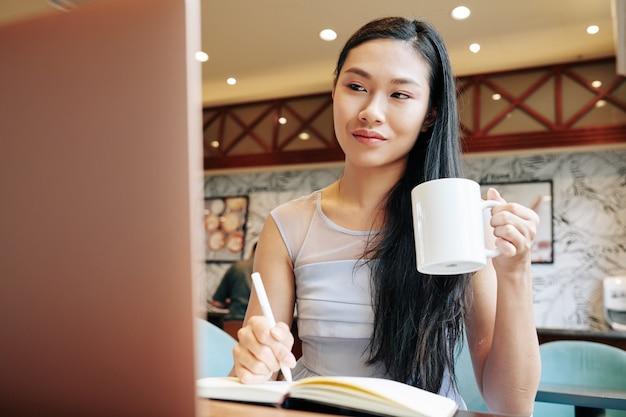 카페에서 모닝 커피를 마시고 노트북으로 뉴스와 이메일을 읽고 패너에 메모를 하는 작은 아시아 여성