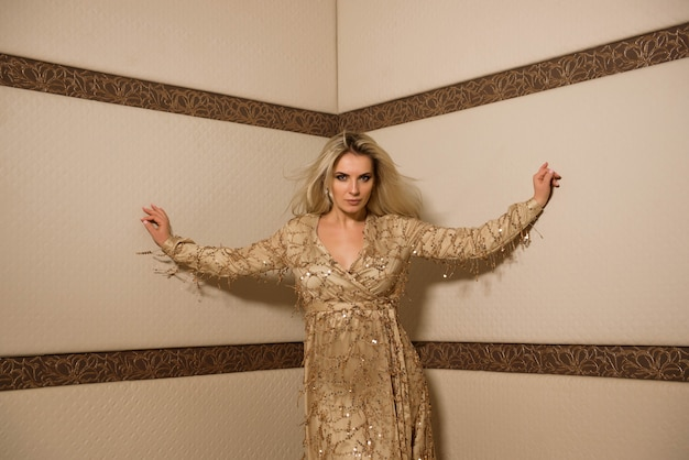 Pportrait of beautiful plus size curly young blond woman posing in a corner of the room.