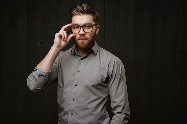 Портрет стильного бородатого мужчины в очках и рубашке, смотрящего вперед, изолированного на черной деревянной поверхности