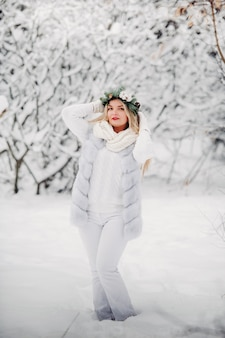 寒い冬の森で白い服を着た女性のpportrait。雪に覆われた冬の森で頭に花輪を捧げる少女。