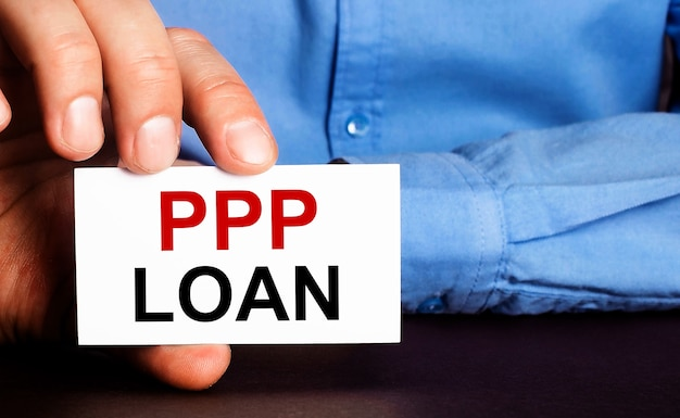 Ppp loan is written on a white business card in a man's hand. advertising concept