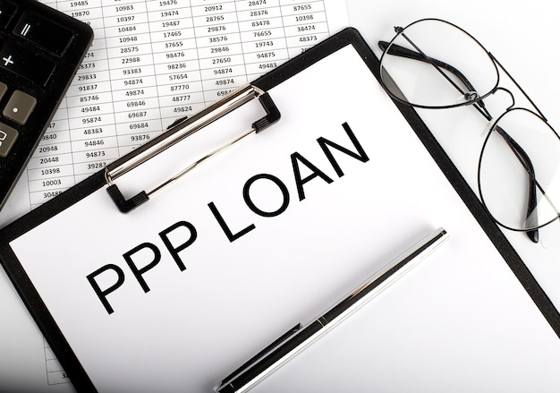 Ppp loan text with calculator, glasses and pen on the chart background