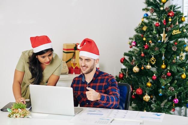 Менеджеры проектов в шляпах санта-клауса обсуждают отчет на экране ноутбука в оформленном офисе