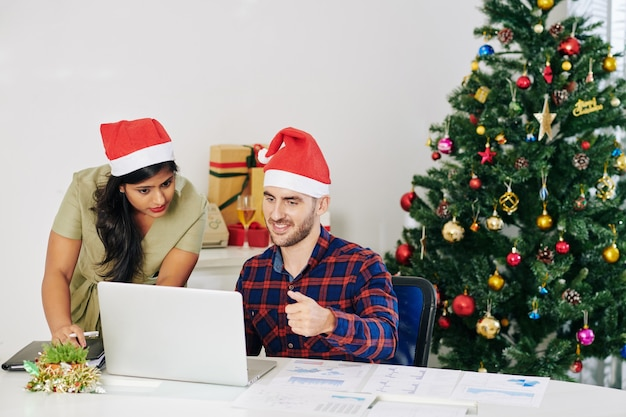 Pproject managers in santa claus hats discussing report on laptop screen in decorated office