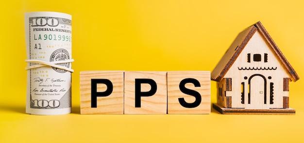 Pps с миниатюрной моделью дома и деньгами на желтом фоне.