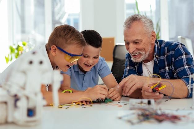Практическое занятие. хороший умный мальчик сидит вместе со своим учителем во время урока естествознания