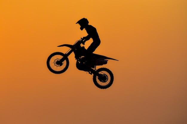 День практики, силуэт мотоциклетного мотокросса, прыгающего на фоне заката.