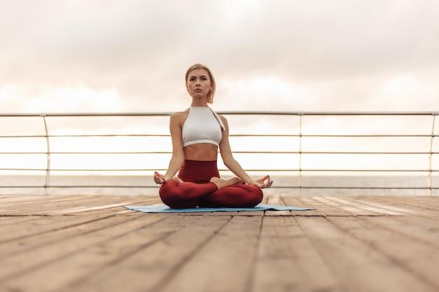 Практика йоги утром на открытом воздухе молодая женщина-йогин в спортивной одежде сидит в позе лотоса на пляже