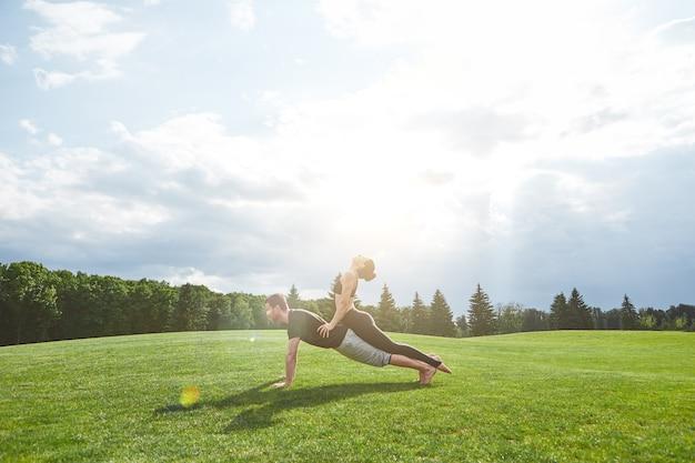 함께 아크로 요가를 연습하는 강한 남자는 자연의 풀밭에 판자에 머물고 있다