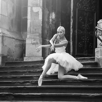 どこでも練習。階段で踊るバレリーナの屋外モノクロソフトフォーカスショット