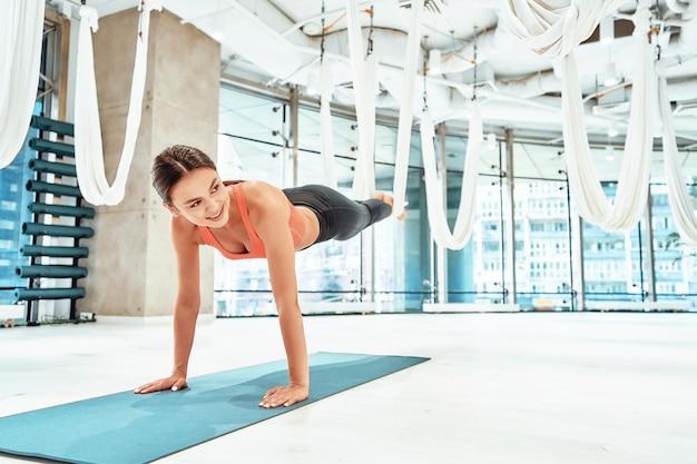 Практика мух-йоги в помещении в полный рост молодой красивой женщины фитнеса в спортивной одежде, использующей