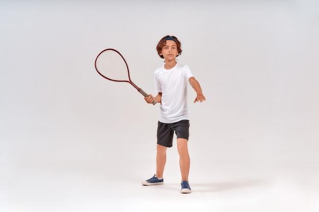 テニスラケットを持って孤立した目をそらしている10代の少年のテニスのフルレングスショットの練習