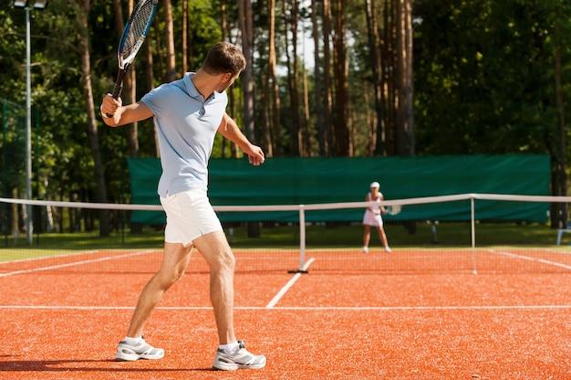친구와 연습. 테니스 코트에서 테니스를 치는 남녀의 전체 길이