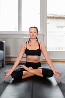 Practicing yoga lotus position at home concept