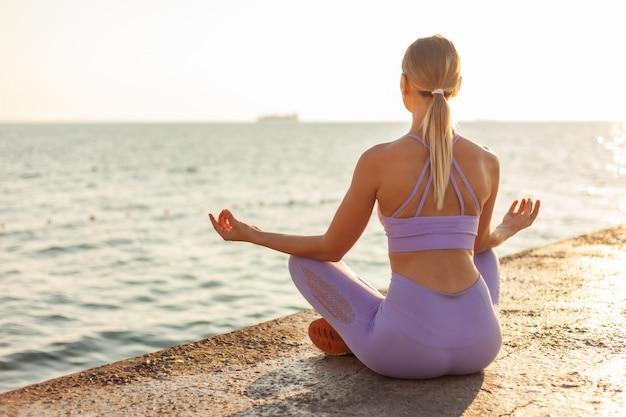 ヨガの練習。日の出の瞑想。ビーチで蓮華座に座っている若いスリムな女性。健康的なライフスタイルのコンセプト