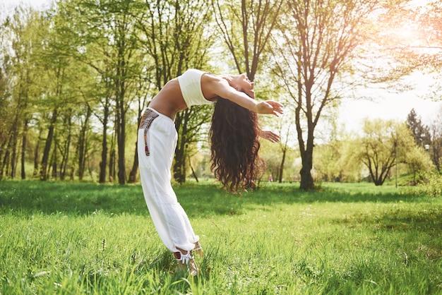 太陽の言葉の下でハーブで朝の美しい少女のヨガを練習。
