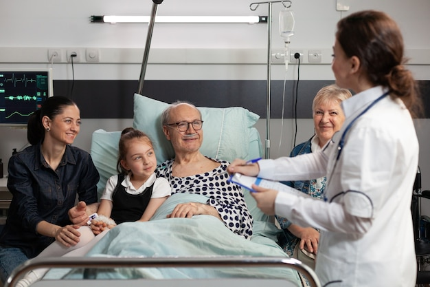 病気の症状を説明する高齢の病気の老人患者を監視する開業医
