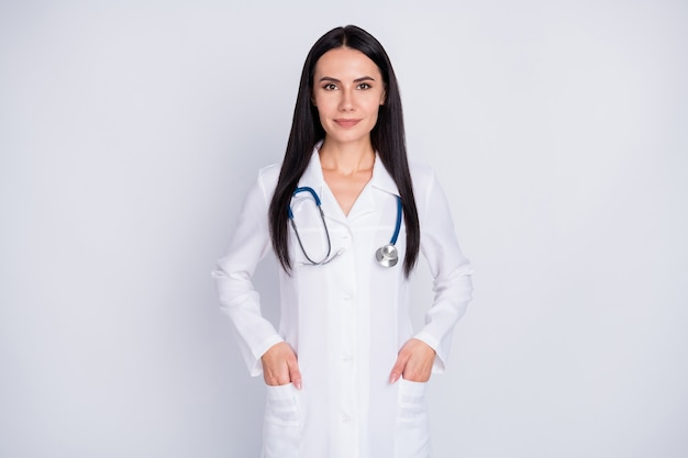 Practitioner girl stand on grey background put hands in pocket white lab coat