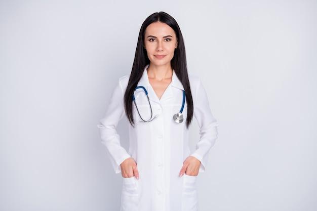 開業医の女の子は灰色の背景に立ってポケットの白い白衣に手を入れます