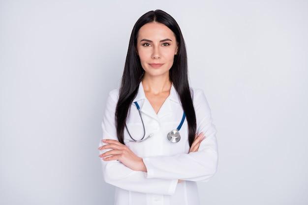 Практикующая девушка в белом лабораторном халате со скрещенными руками на сером фоне