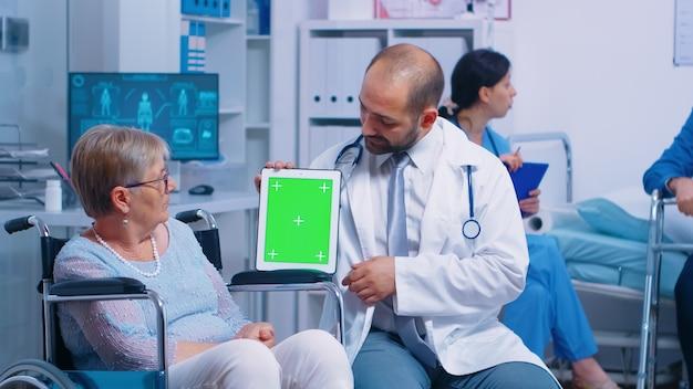 노인 장애인 환자를 위한 회복 센터에서 모형 태블릿을 들고 있는 개업의. 앱, 텍스트, 비디오 또는 디지털 자산을 쉽게 교체할 수 있는 격리된 크로마 그린 스크린. 건강 관리 의학