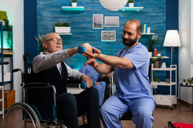 Practitioner man doctor helping retiree senior male in wheelchair to do physiotherapy strength exercise
