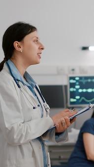 회복 검진 중에 걱정하는 아버지와 의료 전문 지식을 논의하는 개업의 여성 의사