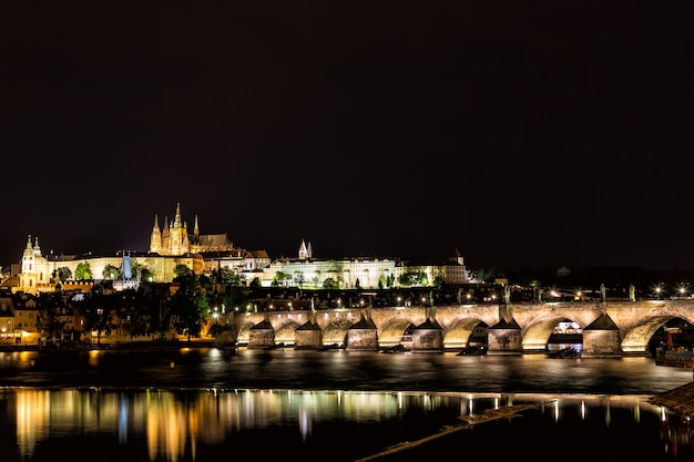 The prague castle and the charles bridge over vltava river with nice water reflections at night in prague