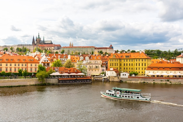 Городской пейзаж праги с прогулочным катером на реке, чешская республика. европейский город со старинными архитектурными зданиями, известное место для путешествий и туризма.