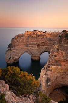 Бухта прайя-да-маринья со знаменитым центром естественных арок в алгарве, португалия