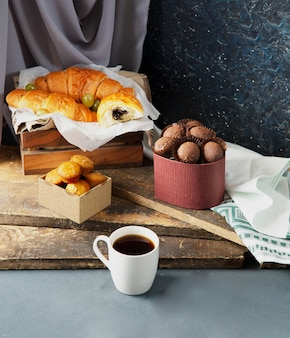 Pralines, muffins, croissants and a cup of coffee