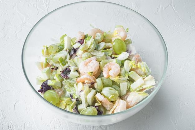 흰색 바탕에 양상추, 체리 토마토, 드레싱, 딜 세트, 소스 사과와 포도를 곁들인 새우 칵테일