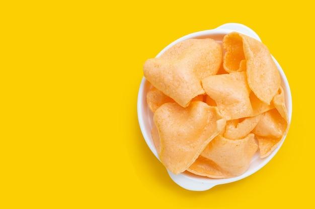 노란색 배경에 흰색 그릇에 새우 크래커입니다. 새우볶음밥
