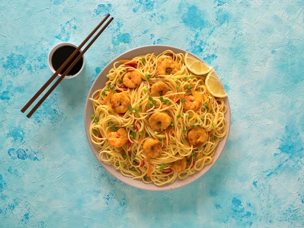 Prawn schezwan noodles with vegetables in a plate on a blue table. top view