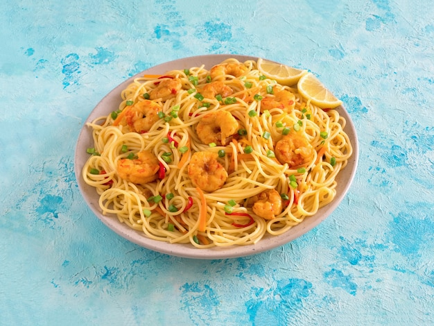 Prawn schezwan noodles with vegetables in a plate on a blue table