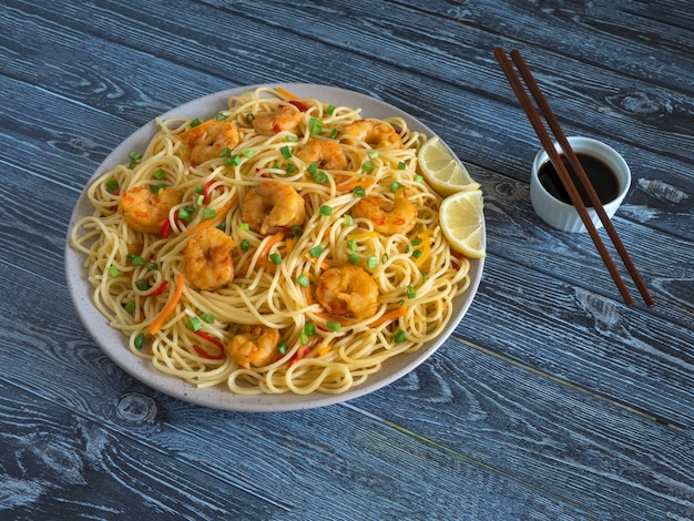 Prawn schezwan noodles with vegetables in a plate