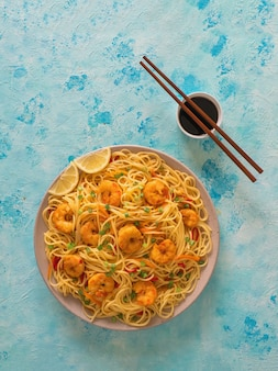 Prawn schezwan noodles with vegetables in a plate.