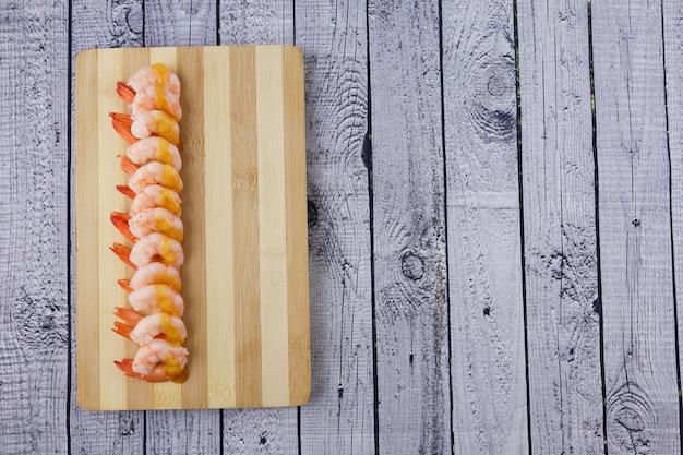 まな板の木製テーブルで調理したエビ