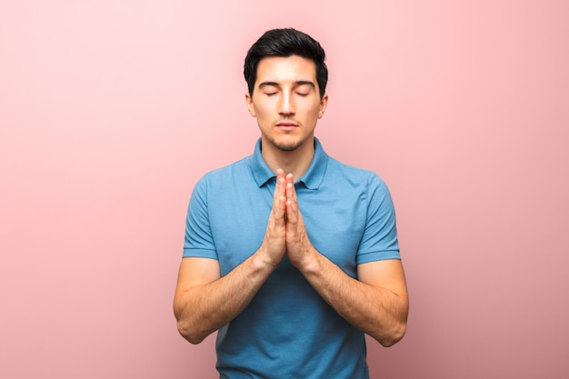 Pray for america. man in blue shirt praying for the world swallowed by coronavirus pandemic against red pink background