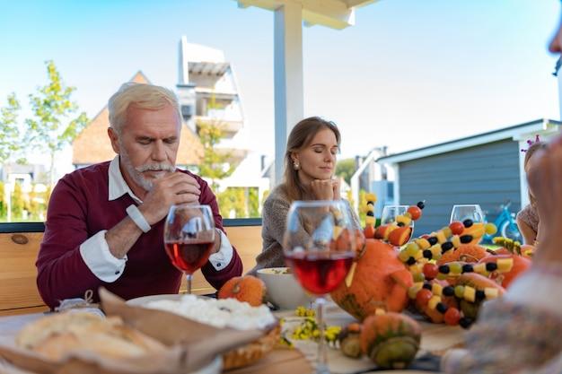 가족을 위해기도하십시오. 저녁 식사를 위해 감정적으로 준비하는 동안 친절한 남성 사람이 테이블에 팔꿈치를 기대고