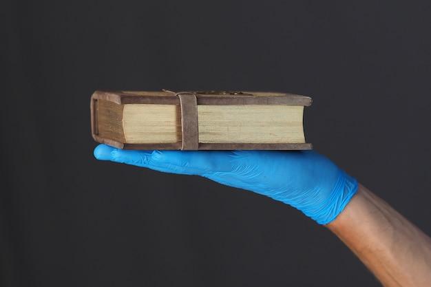 青い医療用手袋で男性の手に祈りの本。
