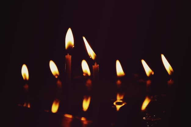 Молитвенные свечи горят в темной церкви