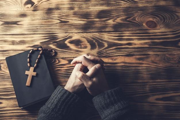 木製のテーブルの上の聖書の祈りの人の手の十字架