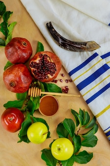 Prayer talit with shofar and traditional food for rosh hashanah. jewish new year.