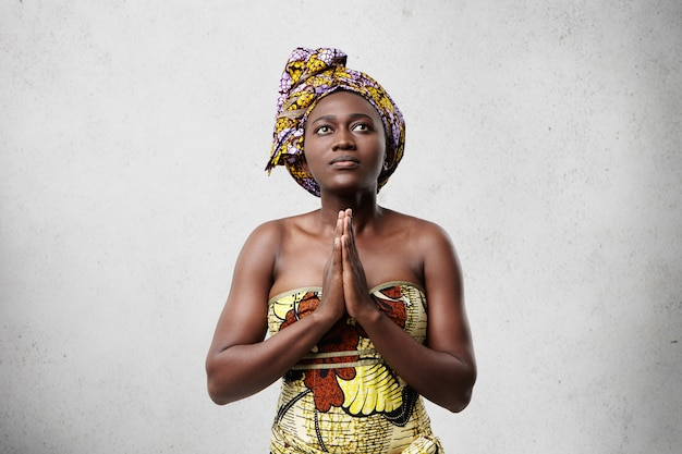 Praying african model with big dark eyes, smooth skin and stubby nose wearing traditional scarf and dress. hopeful dark-skinned middle-aged woman keeping her beautiful hands together while worshiping