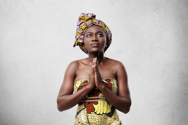 Pregando modello africano con grandi occhi scuri, pelle liscia e naso tozzo che indossa sciarpa e vestito tradizionali. promettente donna di mezza età dalla pelle scura che tiene insieme le sue belle mani mentre adorava