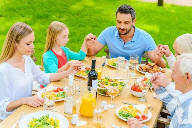 저녁 식사 전에 기도합니다. 야외 테이블에 앉아 저녁 식사 전에 손을 잡고 기도하는 5명의 가족의 상위 뷰