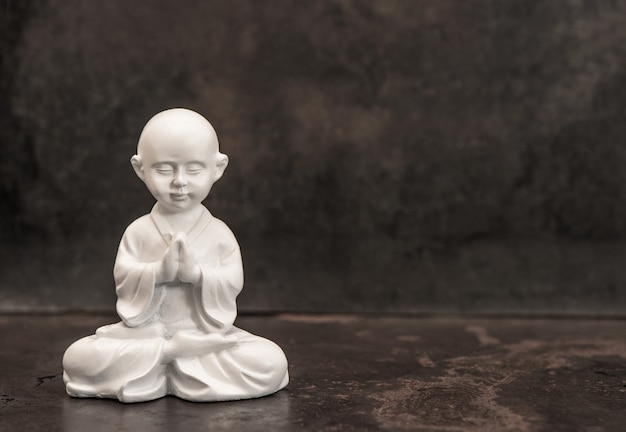 Praying buddha. white monk statue on dark background. meditation concept