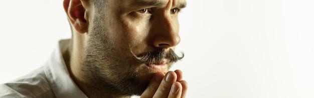Praying. caucasian young man's close up cropped shot on studio wall.
